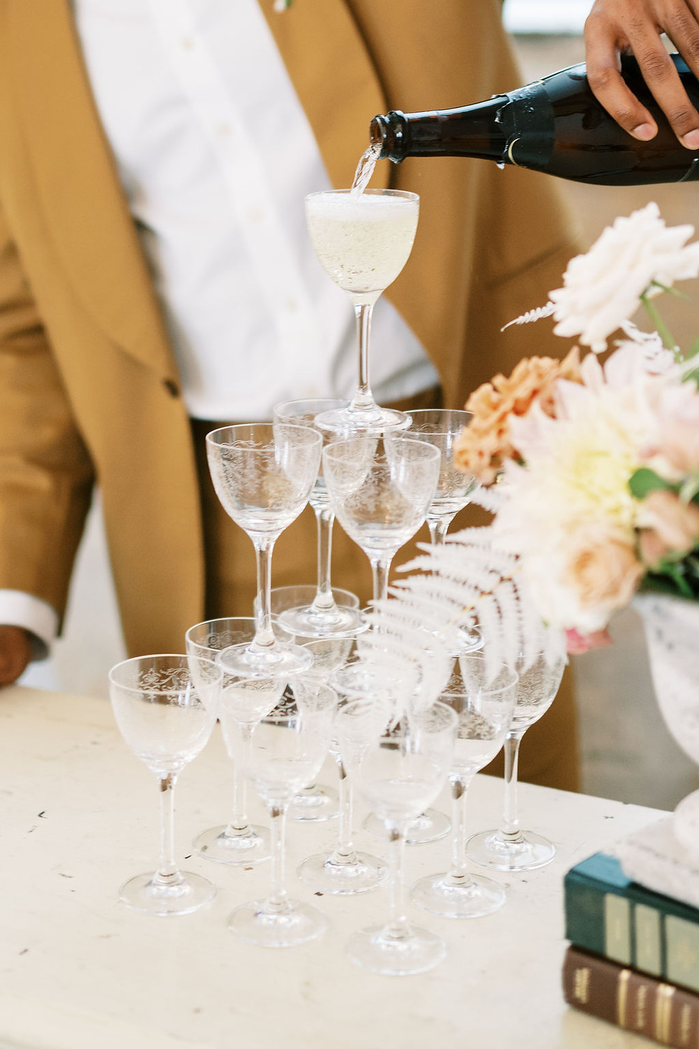 Groom Pouring Champagne Tower to Celebrate the Bridgerton Inspired Wedding at the Marigny Opera House in New Orleans with Decor and Vintage Furniture by Lovegood Rentals Featuring Antique Off White Buffet, Vintage Books and Overgrown Florals