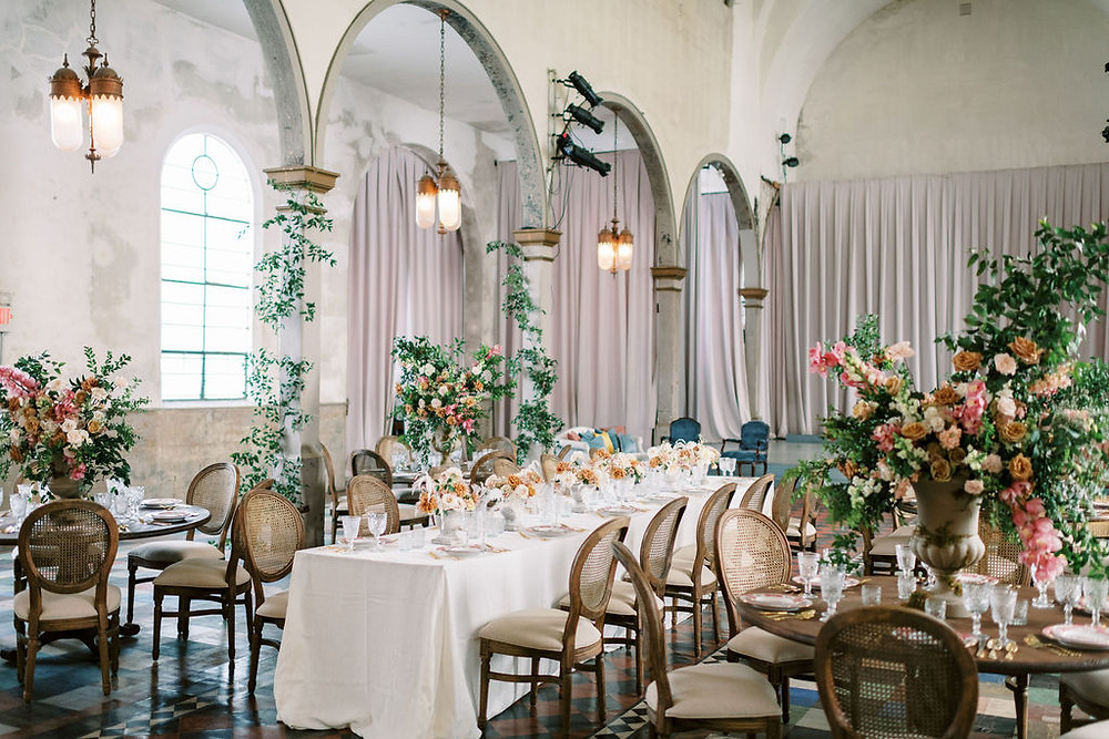 Seated Dinner for Bridgerton Inspired Wedding at the Marigny Opera House in New Orleans with Decor and Vintage Furniture by Lovegood Rentals Featuring Caned Louis Chairs, Round Wooden Tables, Linen Tables and Mixed Cream Florals