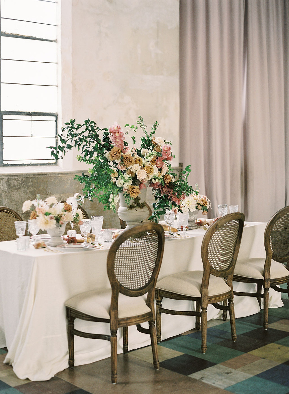 Seated Dinner for Bridgerton Inspired Wedding at the Marigny Opera House in New Orleans with Decor, Lounge Spaces, and Vintage Furniture by Lovegood Rentals Featuring Caned Louis Chairs, Linen Tables and Overgrown Florals