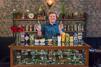 Bartender with Party shirt behind glass, wooden bar topped with lemons, lines, bottles and barbacks behind filled with antique items like books, antique skill, and florals with Lovegood Wedding & Event Rentals - New Orleans Furniture and Decor Company