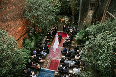 Assorted Aisle of Rugs in Different Colors During a New Orleans Wedding Ceremony in a Courtyard with Family and Friends. Bride is walking down the aisle to her groom with bridesmaids and groomsmen all wearing black suits and dresses. Cafe lights are hanging over head