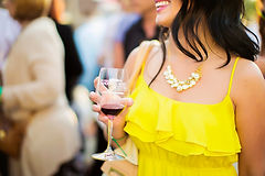 women in yellow dress holding a wine glass with a statement necklace and purse on her shoulder in a crowd of people