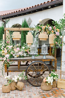 Merchant's Cart for Drink Station During a Event Covered in Florals with Hanging Lanterns. Below are assorted Baskets filled with flowers