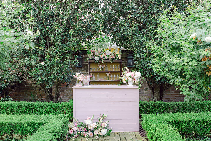 Outdoor Courtyard Space in New Orleans with a Wooden Pink Bar with Barback Cabinet filled with Antique Glasses, Florals and Goblets. Beautiful Pink and Off White Florals Infront of the Bar and Champagne in Ice Bucket on top of Bar