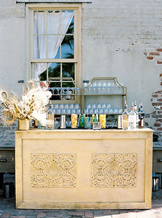 Gold Wooden Bar with Gold India Style Barbacks with Drinking Glasses on them. Large floral and palm arrangement on the corner of the gold bar with bottles, crackers, and stirs