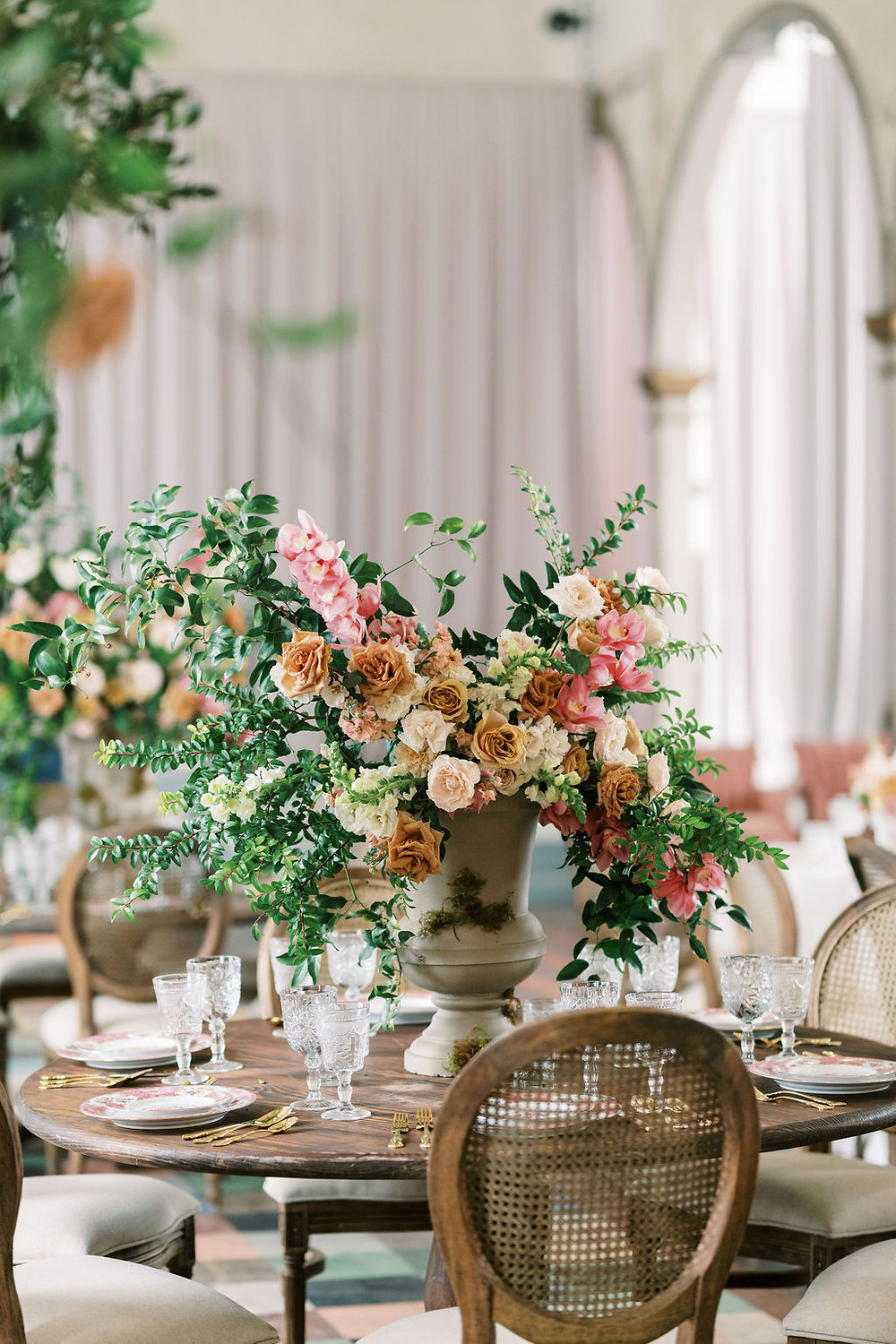 Seated Dinner for Bridgerton Inspired Wedding at the Marigny Opera House in New Orleans with Decor and Vintage Furniture by Lovegood Rentals Featuring Caned Louis Chairs and Mahogany Round Tables and Overgrown Florals