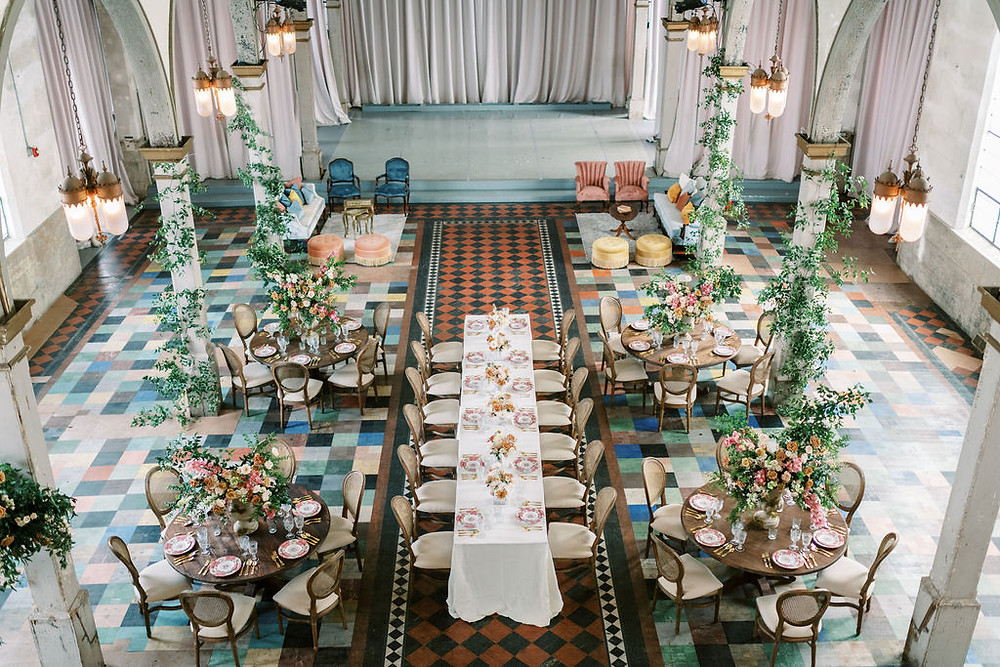 Overview of Seated Dinner for Bridgerton Inspired Wedding at the Marigny Opera House in New Orleans with Decor, Lounge Spaces, and Vintage Furniture by Lovegood Rentals Featuring Caned Louis Chairs, Mahogany Round Tables and Overgrown Florals