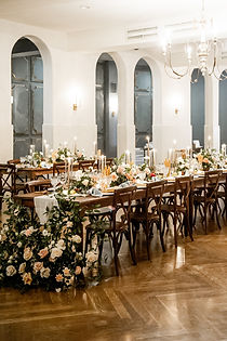 Wooden Tables with Large Floral arrangements on the ends. Linen Runners down the middle of the mahogany tables with florals, fruits, cnadlesticks with glass covereings. Mahogany Crossback Chairs on both sides of the farm tables with place settings and bread per place. Inside Il Mercato in New Orleans with white walls, wooden chevron floors and french style chandeliers