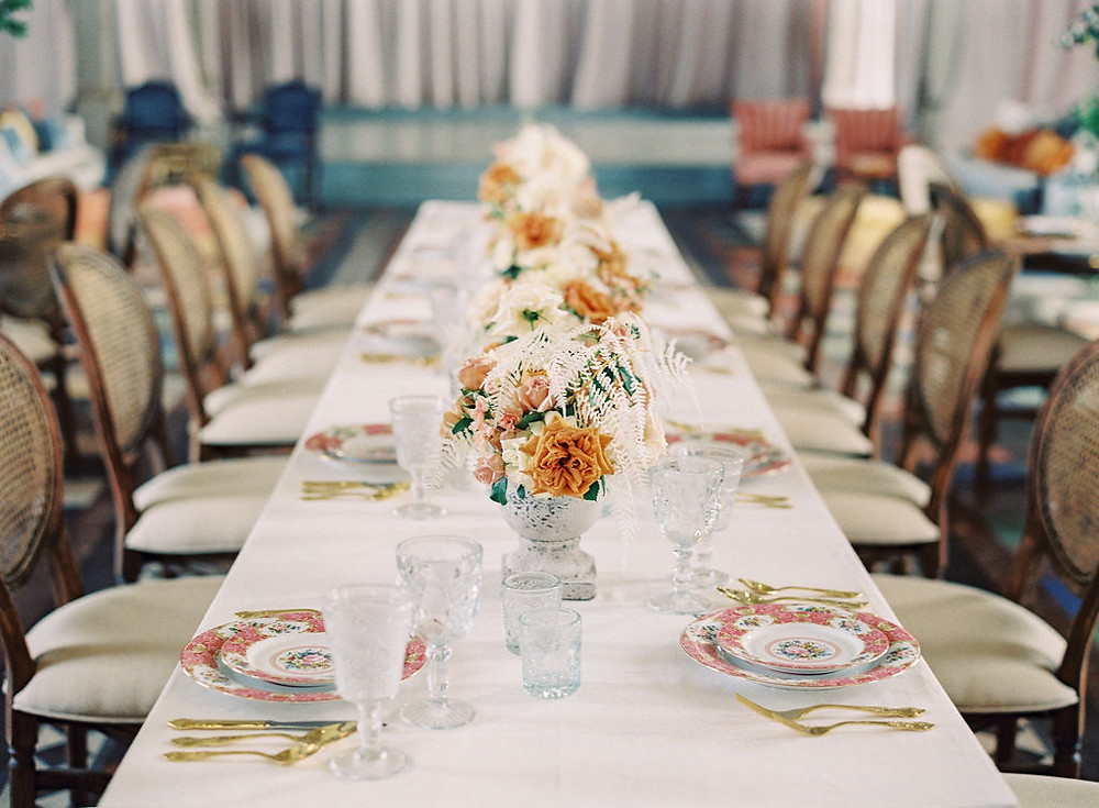 Seated Dinner for Bridgerton Inspired Wedding at the Marigny Opera House in New Orleans with Decor, Lounge Spaces, and Vintage Furniture by Lovegood Rentals Featuring Caned Louis Chairs, Gold Flatware and Overgrown Florals