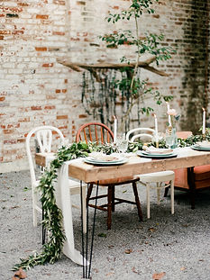 Hairpin Wooden Table with a runner and garland going down the middle with white and brown mismatched wooden antique charis in a brick courtyard with candlesticks, floral small arrangements and plates with a charger