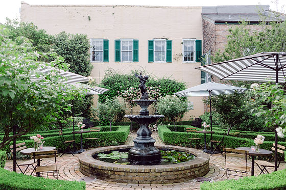 Courtyard with Black, White Stripe Umbrellas with Bistro Tables and Garden, Bistro Chairs. Small Floral Arrangements on the Tables under the umbrellas surrounding the fountain in the middle of the French Quarter Courtyard with Green Shutters on the Building. Behind the Fountain is a floral display of pink and off white flowers