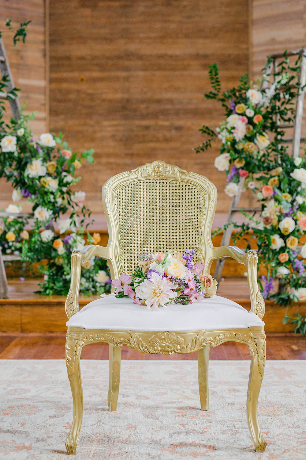 Spring Fruit Wedding in Old New Orleans Church | Complete Upholstered Ceremony Seating, Lounge Spaces, Farm Tables, and Many More Details with Lovegood Wedding & Event Rentals | Lovegood Wedding & Event Rentals, New Orleans Vintage Rental Company for Corporate, Parties, and Weddings | Lounge Furniture in NOLA, Specialty Rentals, Decor across the Southeast, Velvet Furniture Ceremony Wooden Ladders Covered in Florals