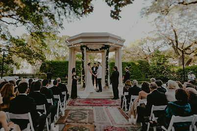 Bride and Groom getting married outside at the Elms with family and friends. Aisle lined with antique rugs and white folding chairs with Lovegood Wedding & Event Rentals - New Orleans Furniture and Decor Company