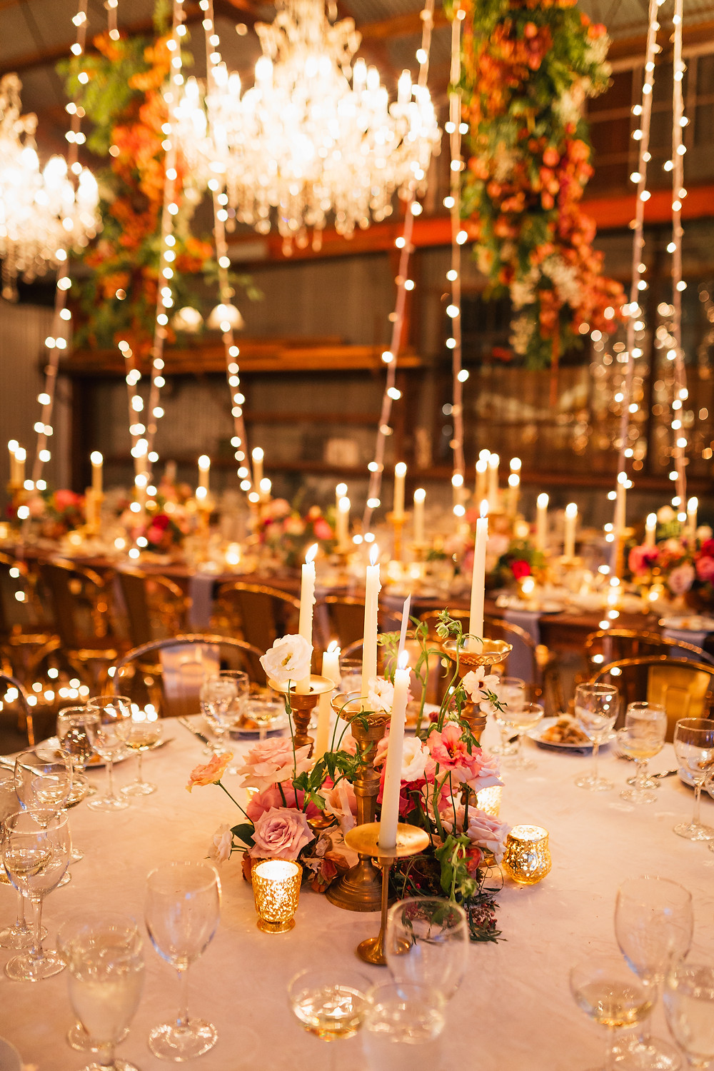Lovegood Wedding & Event Rentals, New Orleans Vintage Rental Company for Corporate, Parties, and Weddings | Lounge Furniture in NOLA, Specialty Rentals, Decor across the Southeast, Classic Farm Tables with Gold Chairs, Florals and Candles in Old Warehouse