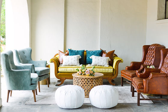 Lounge Space and Furniture inclusing a velvet yellow sofa, 2 mint chairs, and two leather wingback chairs. Assorted Pillows on the sofa and a round coffee table and poufs with a small floral arrangement in an outdoor space with white walls