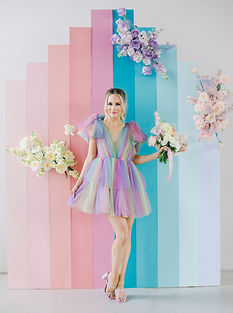 Colorful Backdrop Ombre from Light Peach to Dark Pink Following Turquoise to light Perrywinkle covered with three floral arrangements. Beautiful blonde woman wearing rainbow ombre short tulle dress with light purple heels holding a bouquet of florals