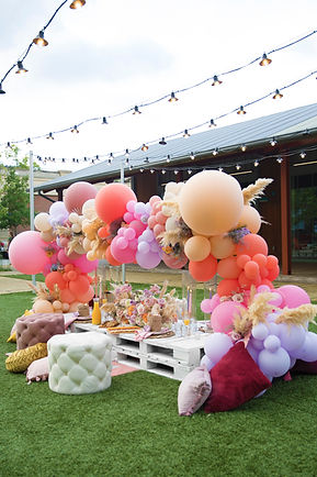 Balloon Arch with pinks, yellows, and light purple ballons and florals. Pallet table with rugs, ottomans, poufs, and pillows from Lovegood Wedding & Event Rentals - New Orleans Furniture and Decor Company with Pillows and Poufs