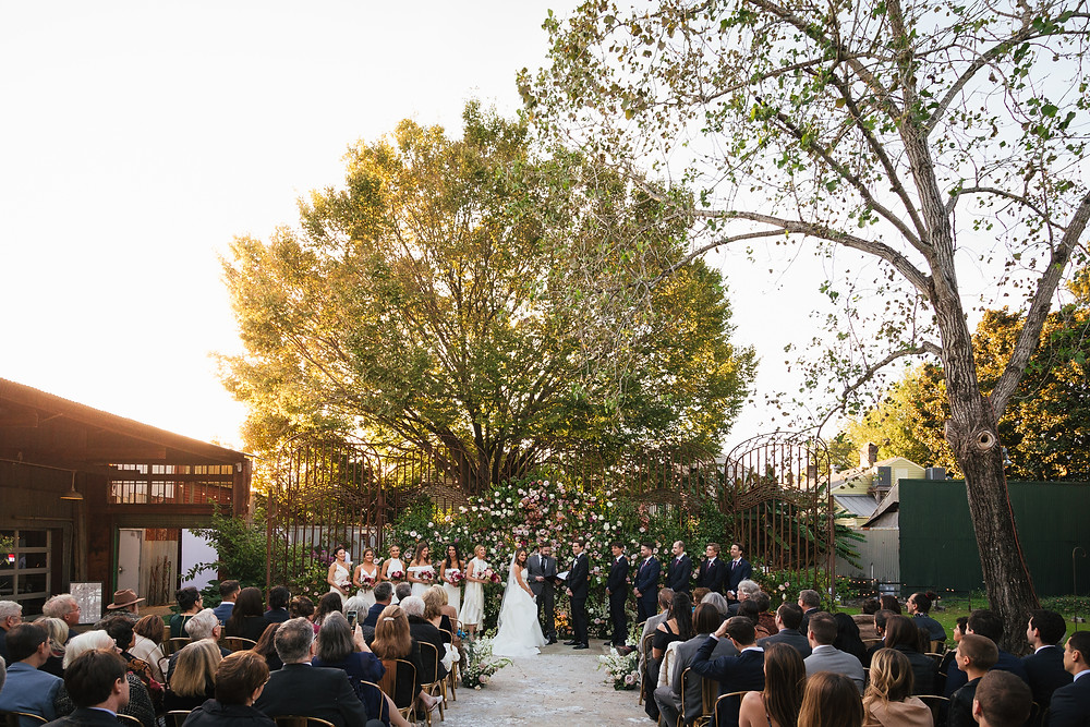 Lovegood Wedding & Event Rentals, New Orleans Vintage Rental Company for Corporate, Parties, and Weddings | Lounge Furniture in NOLA, Specialty Rentals, Decor across the Southeast, Old Warehouse Ceremony with Gold Chairs, Florals and Candles