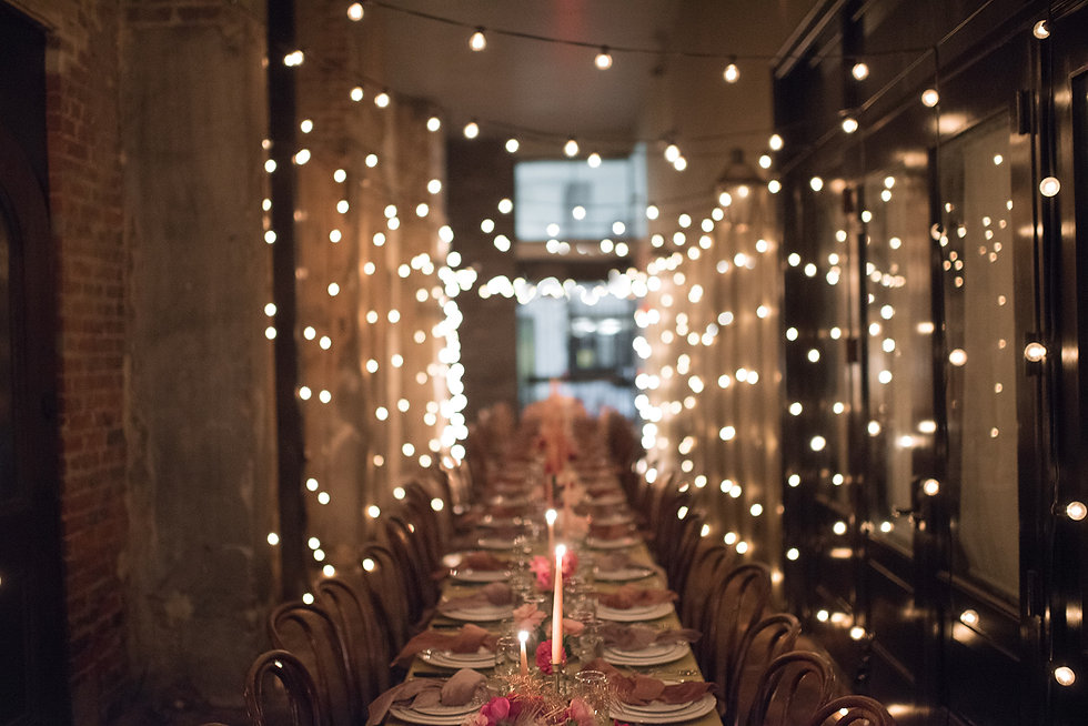 Long Dining Table filled with candles, plates, flatware, velvet napkins. Outdoor space lined with tiny lights and assorted wooden bentwood chairs