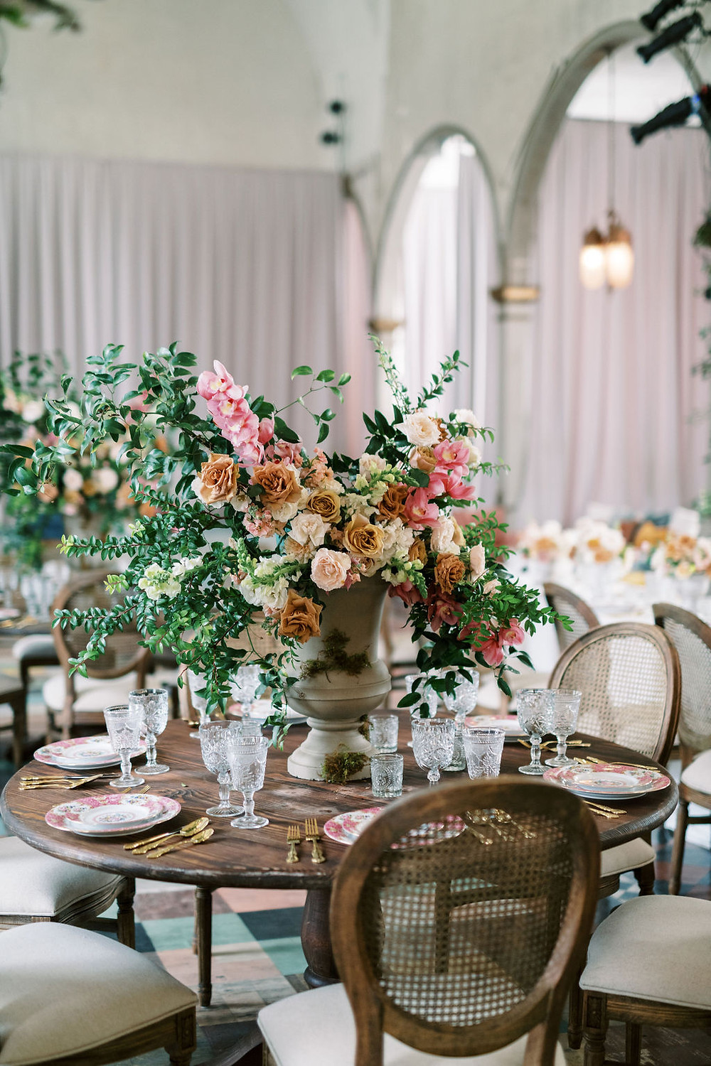 Seated Dinner for Bridgerton Inspired Wedding at the Marigny Opera House in New Orleans with Decor and Vintage Furniture by Lovegood Rentals Featuring Caned Louis Chairs, Mahogany Round Tables and Overgrown Florals