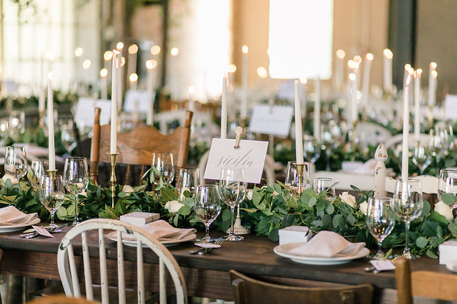 Wooden Tables with Wooden Mismatched Chairs on both sides in brown and white. Garland with roses down the middle of the tables with drinking and wine glasses at each place setting with a napkin, small giftbox, and flatware. Table numbers are small cities the couple visit before getting married