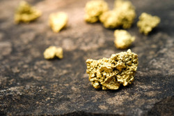 A lump of gold on a stone floor.jpg