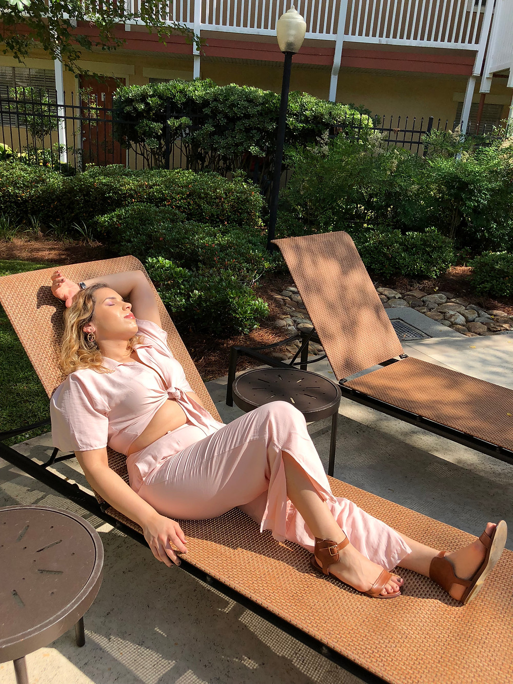 Sunny day laying down with a pink collared culotte set and cognac sandals.