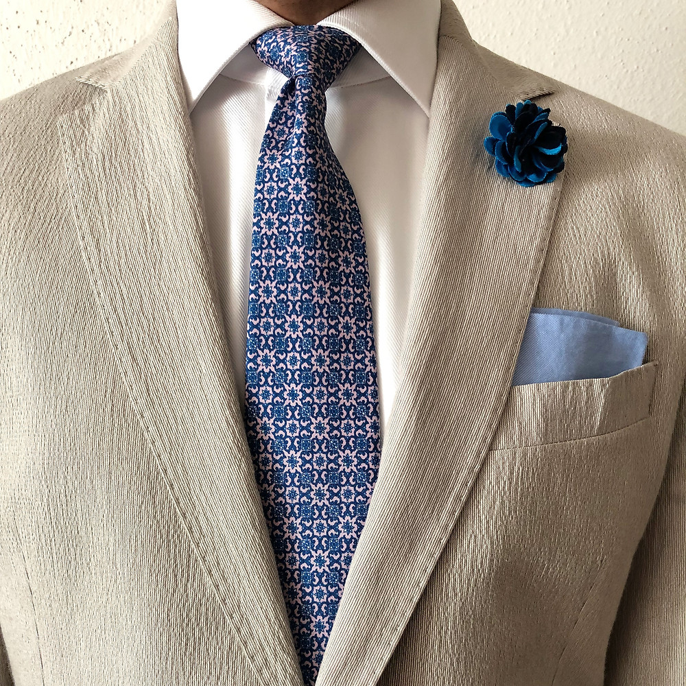 Beige seersucker suit featuring blue an drink pattern tie, light blue pocket square and multi blue color boutonniere