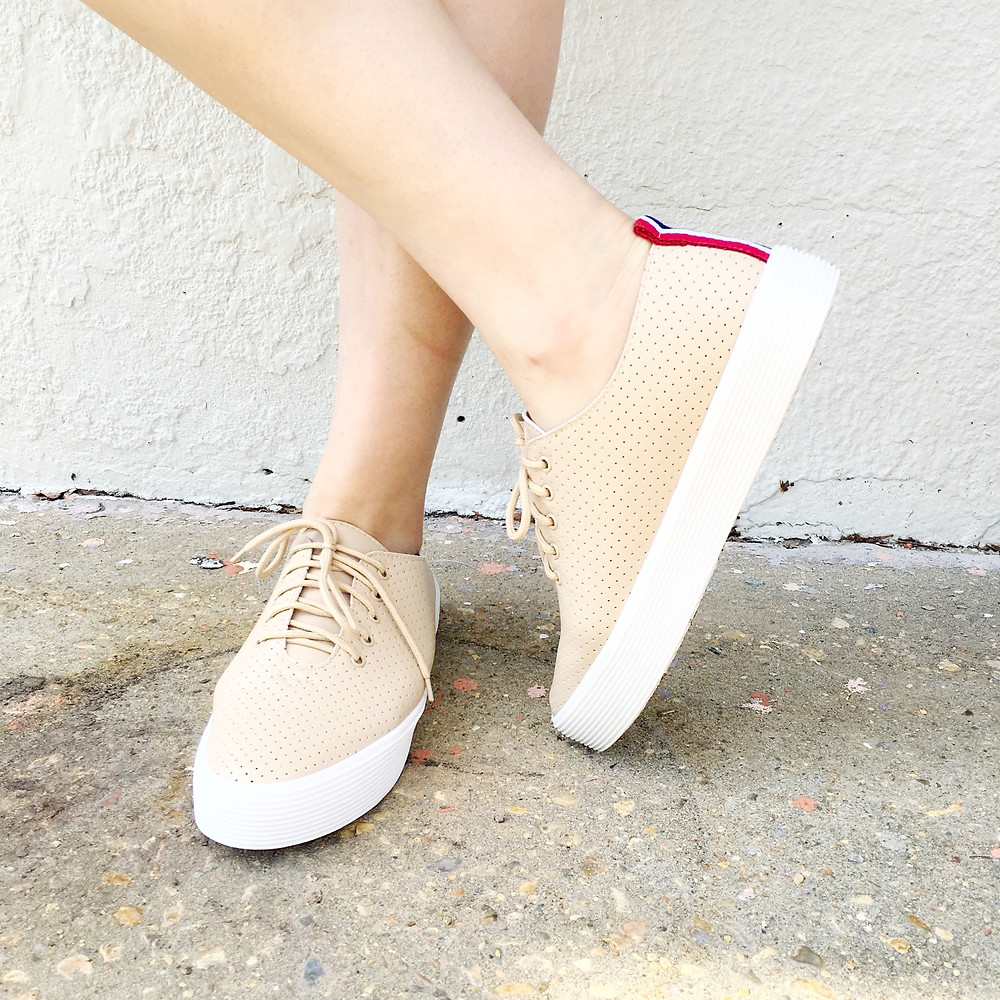 Casual cream color perforated sneaker features white sole and racer stripes at back.