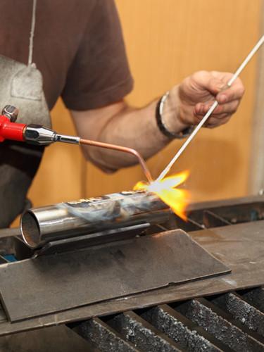 Artist sculptor works on steel tube