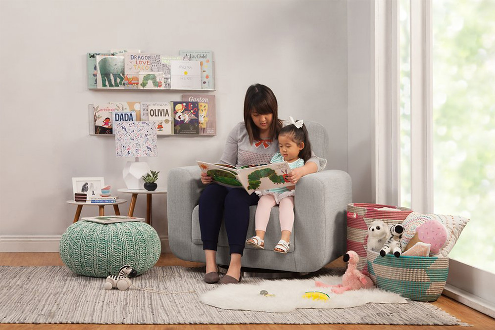 mother and daughter reading a children's book together sitting on babyletto nursing chair