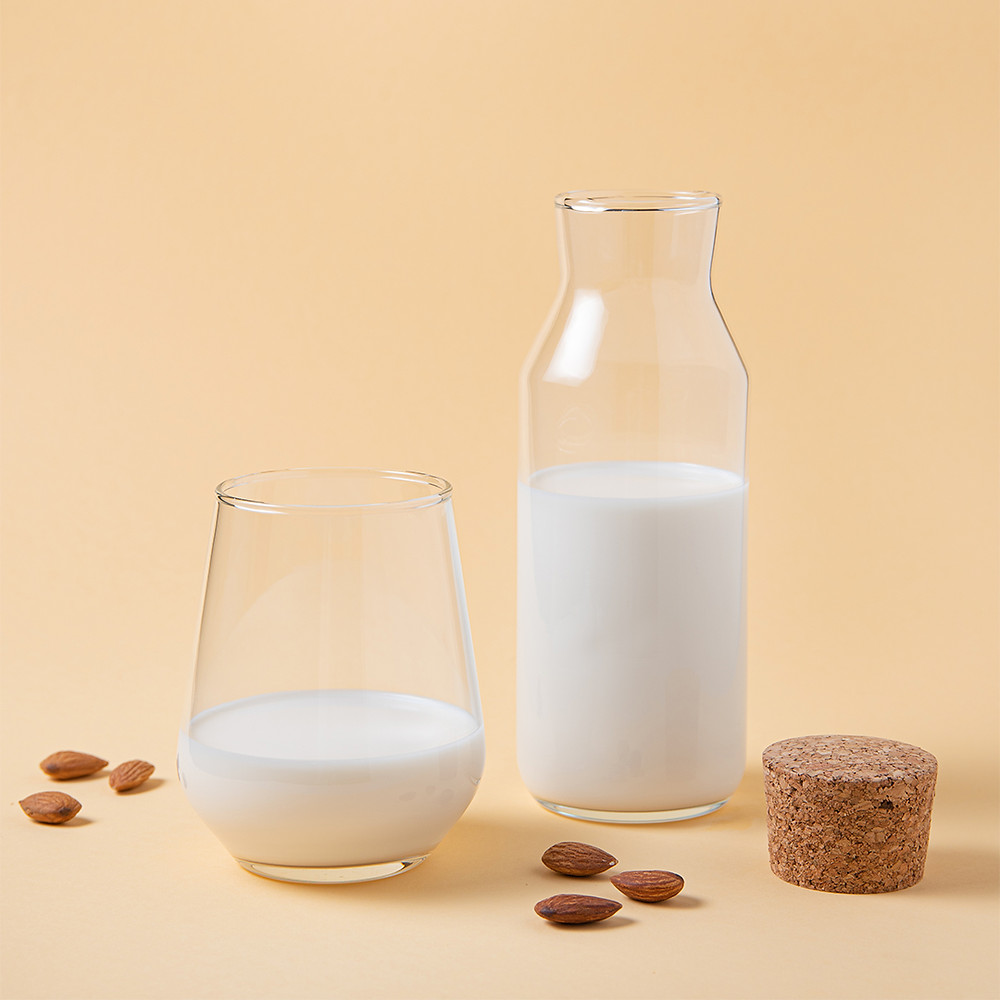 a-glass-and-bottle-of-fresh-vegan-almond-milk-and-a-few-scattered-nuts-on-a-yellow-background
