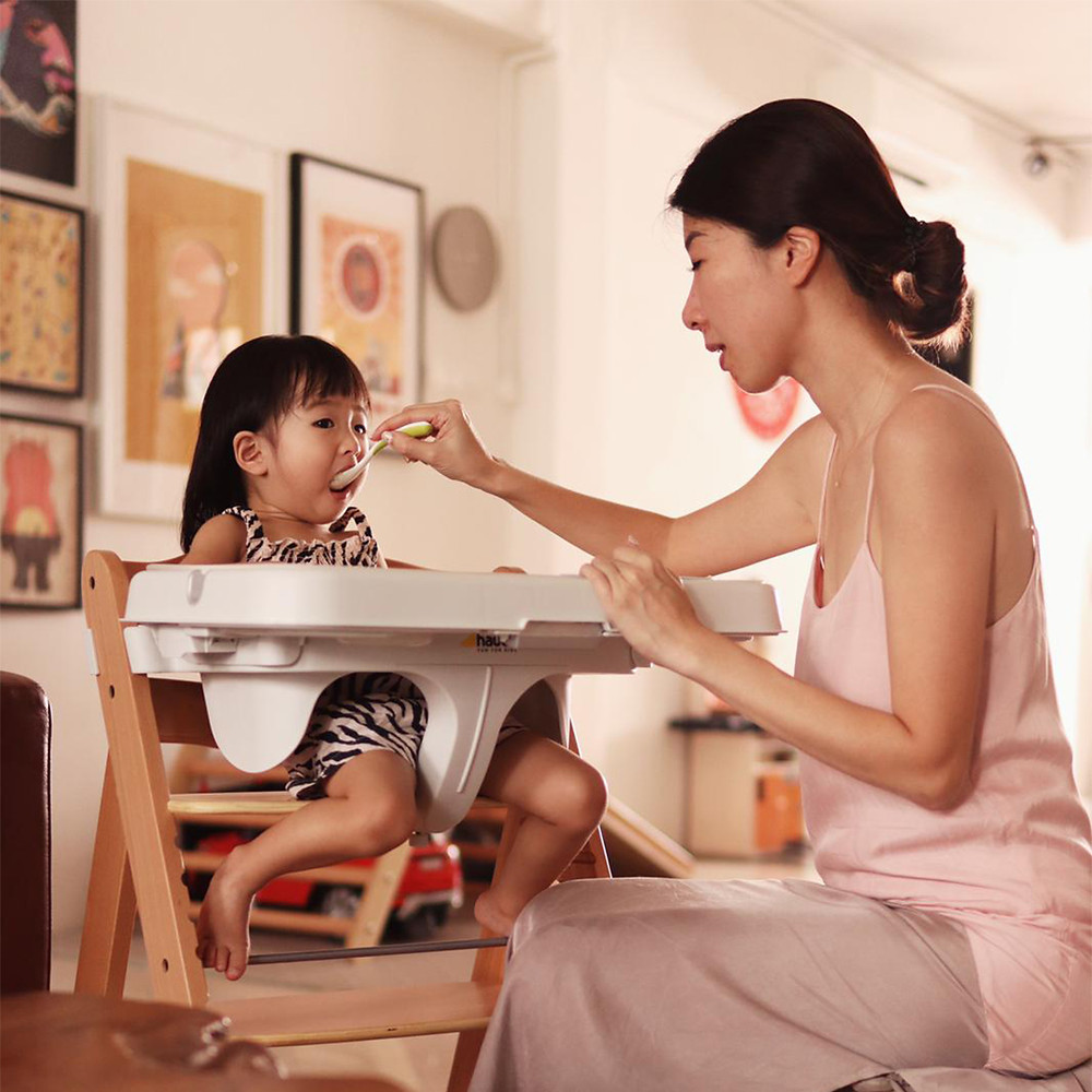 mother feeding her baby that is using alpha chair + tray