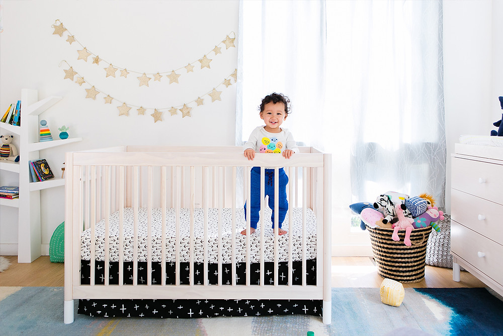 baby standing on a nursery crib