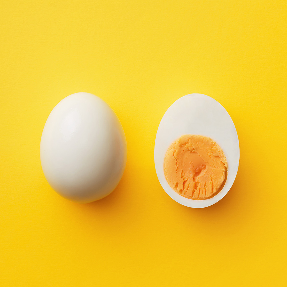 Single-whole-white-egg-and-halved-boiled-egg-with-yolk-on-a-yellow-background
