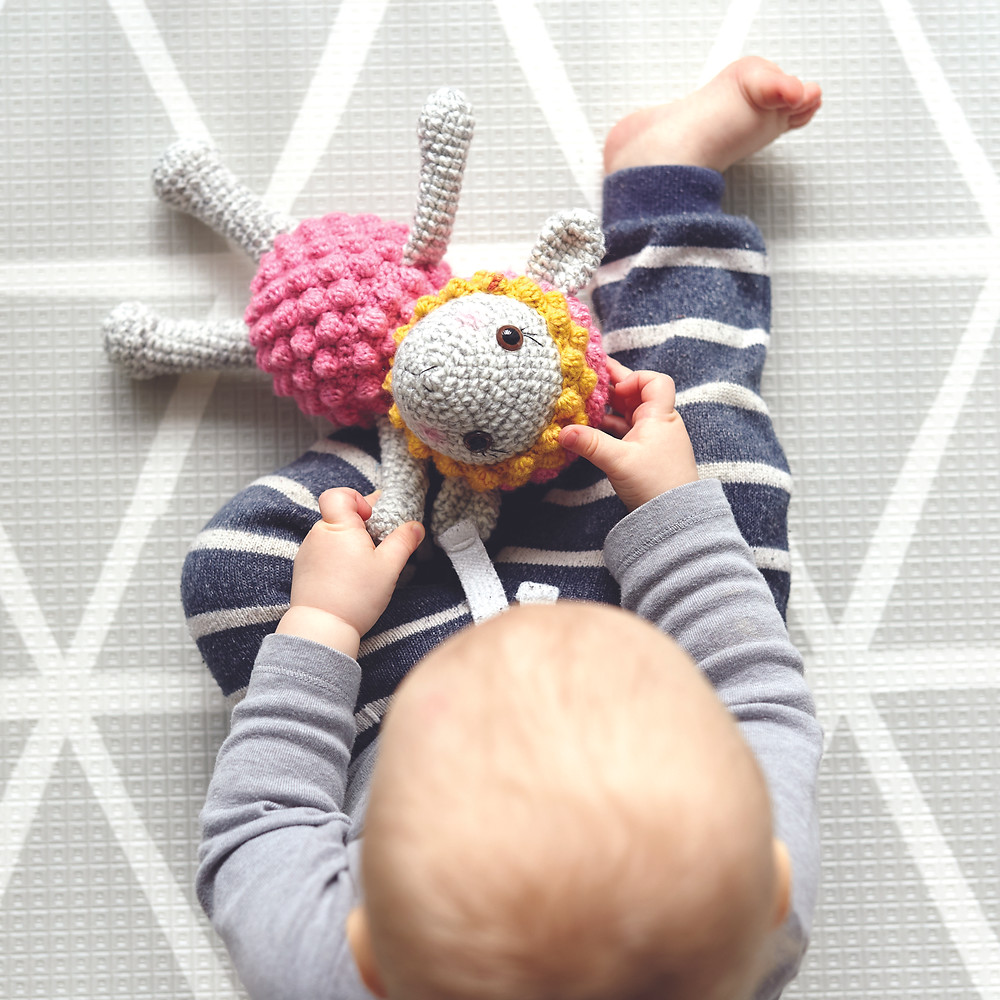 baby playing doll on playmat