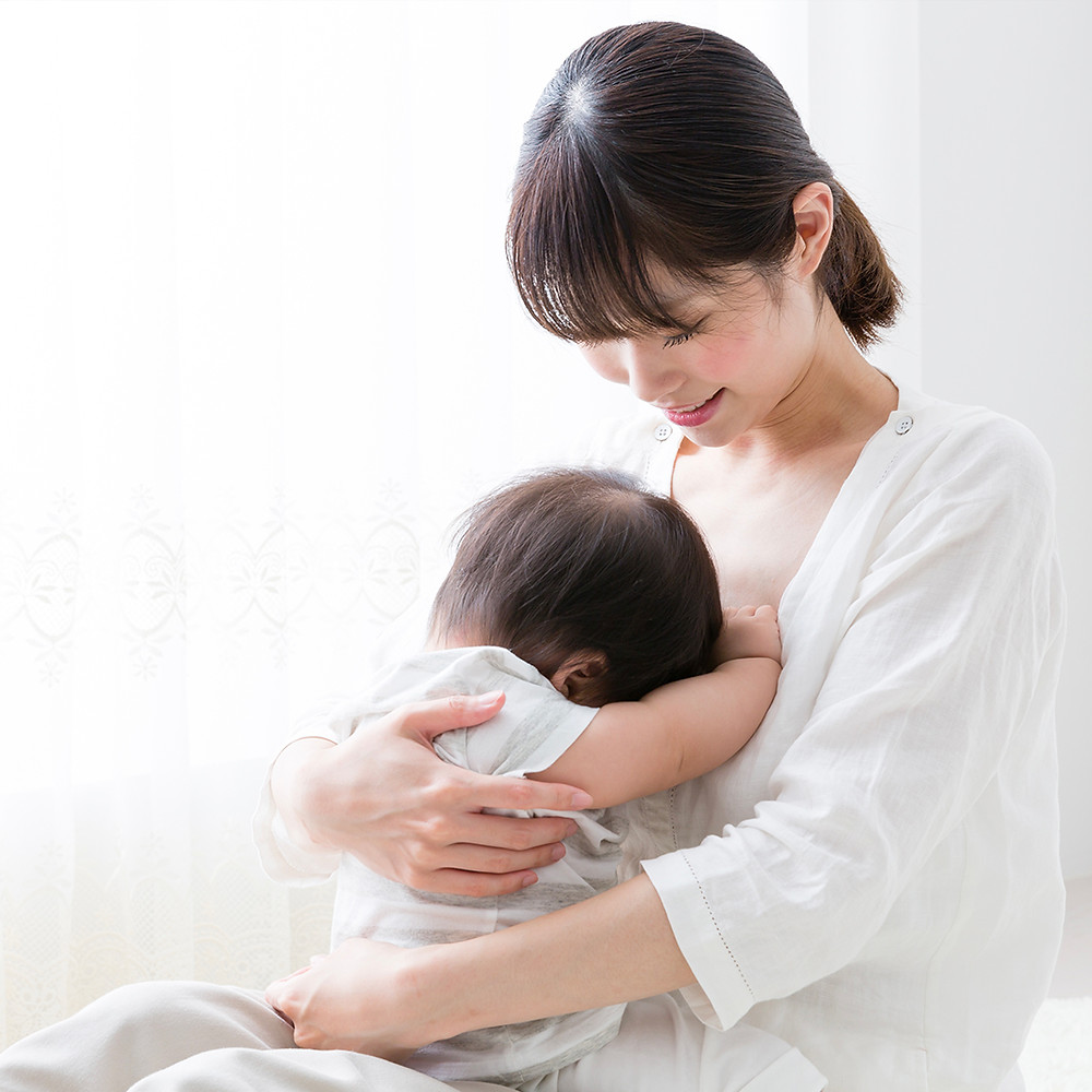 Asian mother playing with baby at home