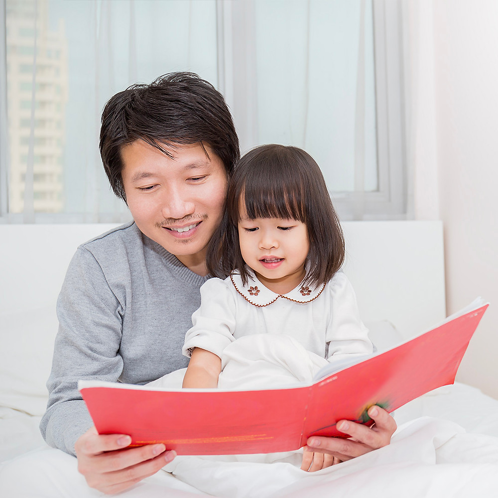 father and child bonding together while reading a book