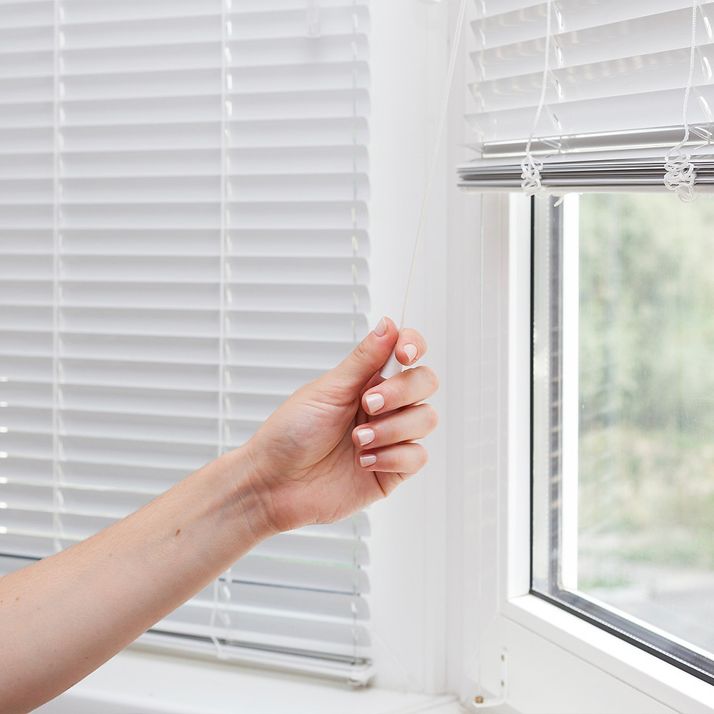woman pulling down window blinds cord