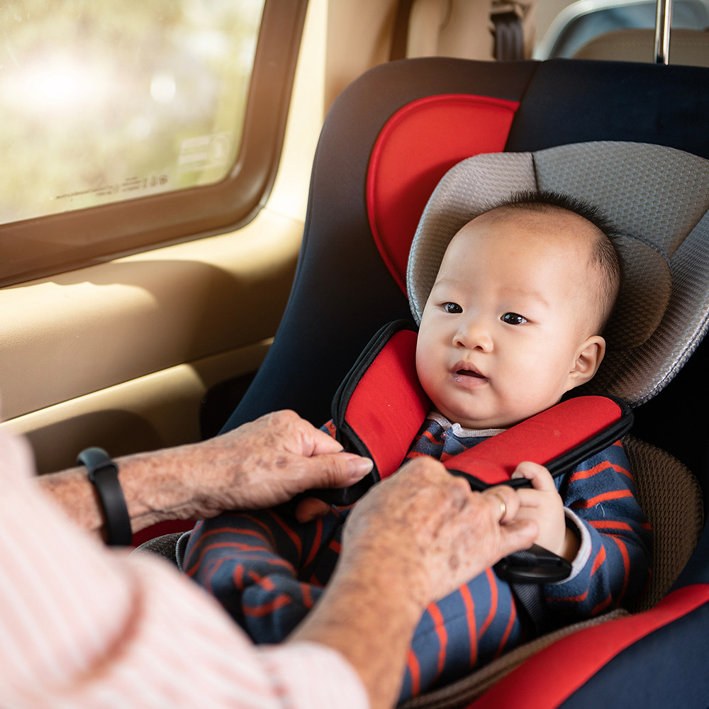 baby getting ready for travel in a car seat