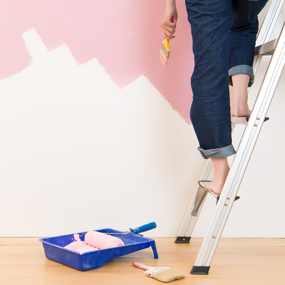 woman standing on ladder doing wall painting