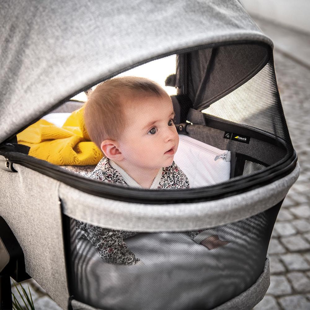 Newborn baby inside a Vision X Grey Stroller