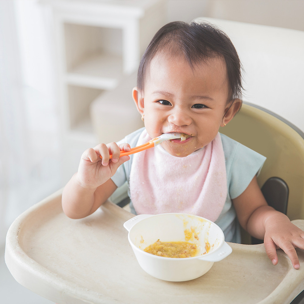 baby eating food while seated on a high chair