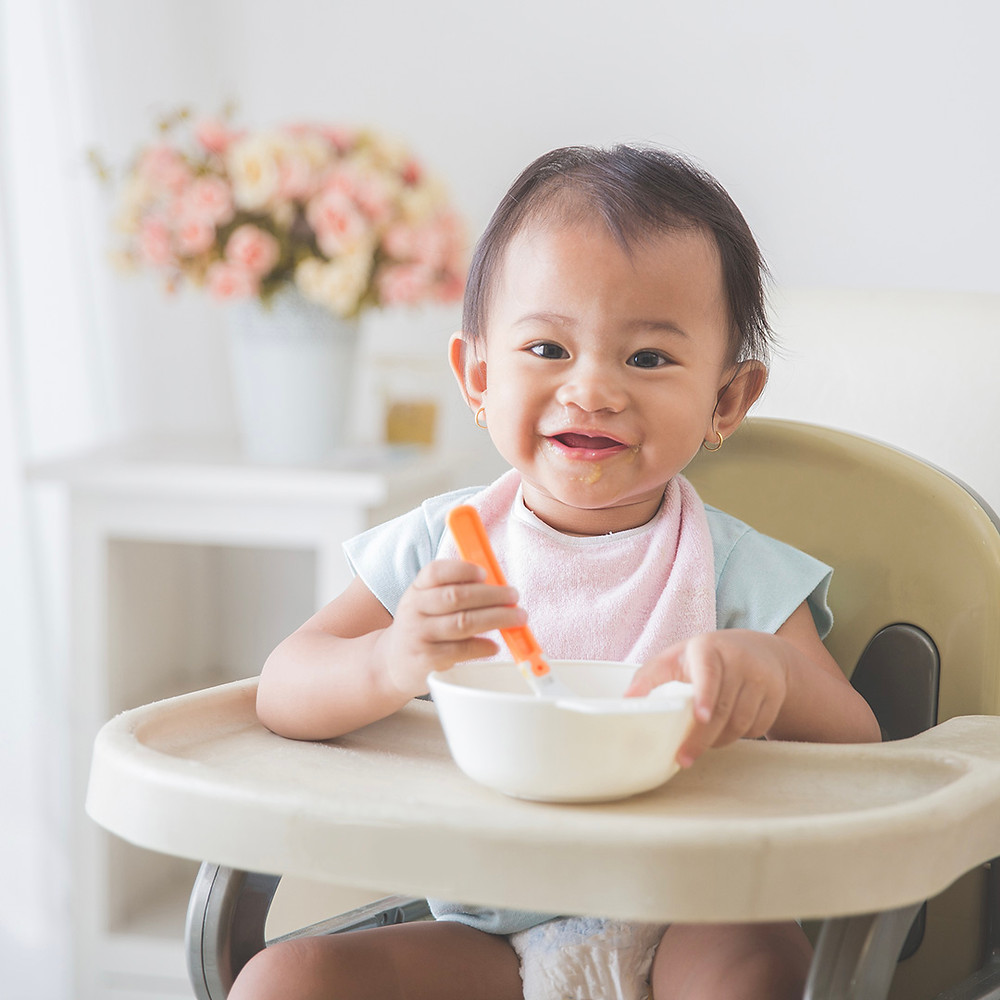 cute baby boy happily eating his mean on high chair
