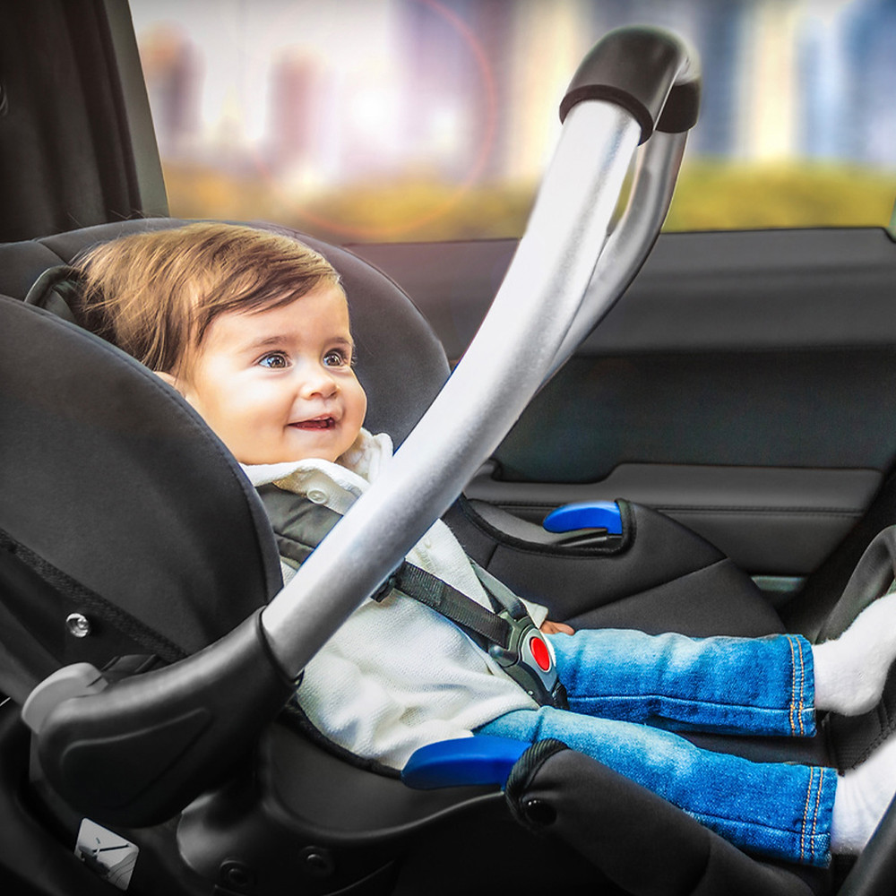 baby sitting on a hauck comfort fix black car seat