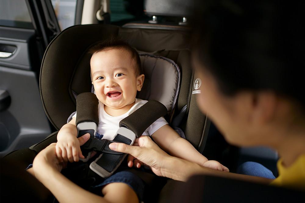 parent making baby sit on car seat
