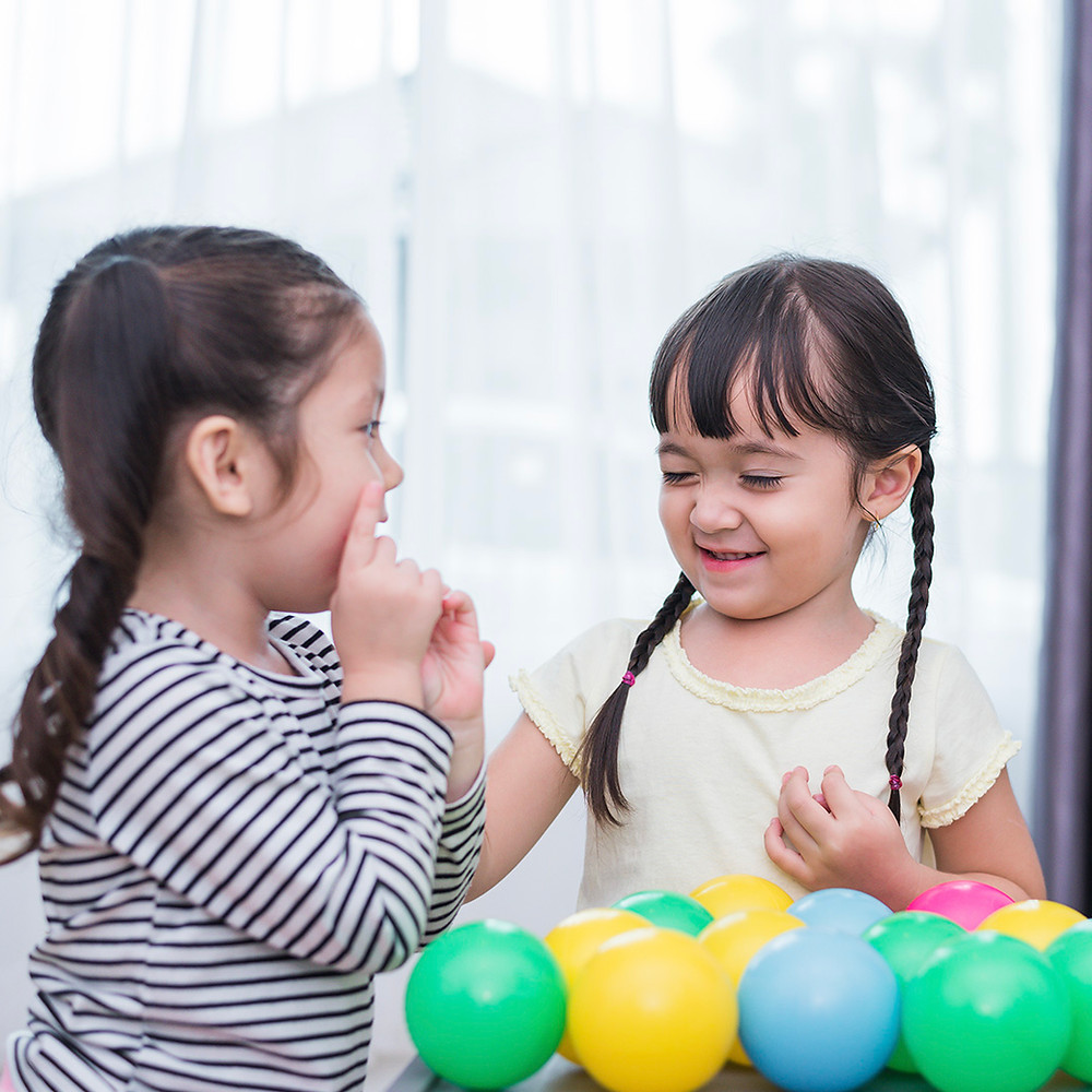 two young girls playing together and having fun