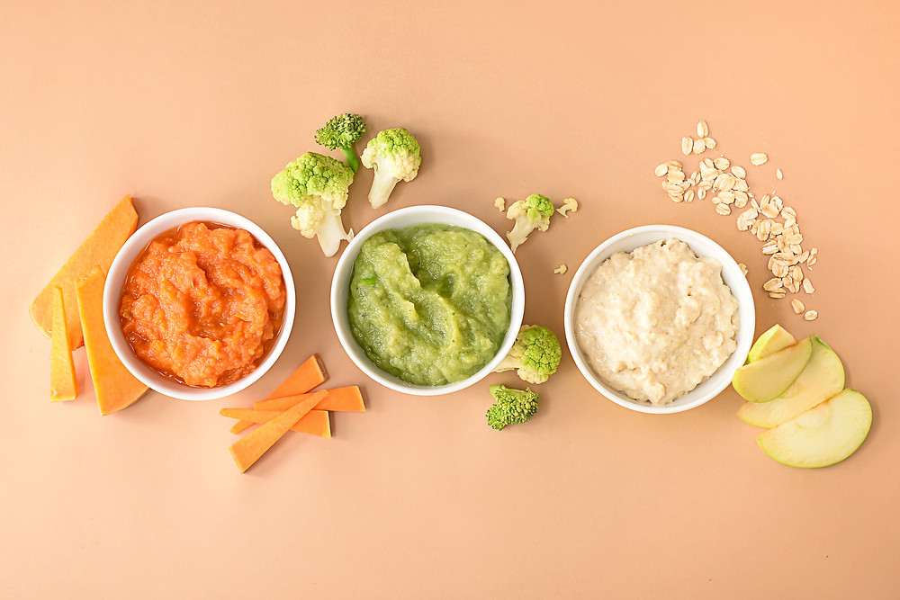 Bowls-with-healthy-baby-food-on-color-background