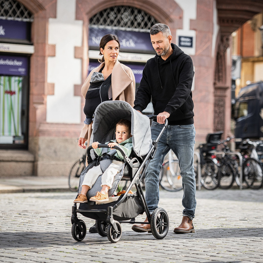 Mother and Father pushing a stroller with their child