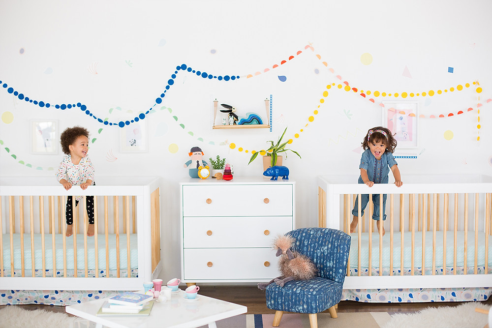 two babies inside a white crib laughing